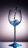 Kleine Menge transparente Flüssigkeit im Weinglas Lizenzfreie Stockfotos