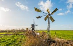 Kleine Metallwindmühle und eine große hölzerne hohle Bockwindmühle in einer DU Stockfotografie