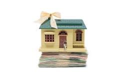 Kleine miniatuurhuis model status op stapel geldbankbiljetten tegen witte achtergrond Stock Foto