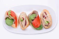 4 kleine Mischungssandwiche mit Pastete und Fleisch, gegrillter Paprika auf einer weißen ovalen Platte stockfotografie