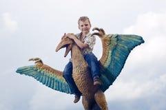 Kleine moedige kinderen op een dinosaurus in een park stock foto