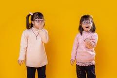 Kleine mooie meisjes die met geestelijke wanorde roze sweaters dragen stock foto