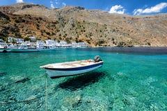 Kleine motorboot bij duidelijke waterbaai van Loutro-stad op het eiland van Kreta, Griekenland Royalty-vrije Stock Foto