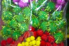 Kleine multicolored pom-poms met glanzende draden in een pakket royalty-vrije stock foto's