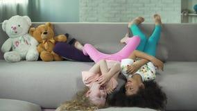 Kleine multiraciale kinderen die op bank thuis liggen en pret hebben, kinderjaren stock videobeelden