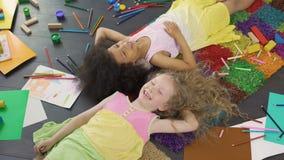 Kleine multiraciale meisjes die op de vloer liggen, en van vakantie genieten lachen stock footage