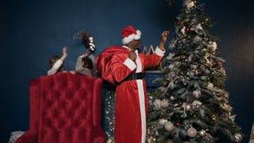 Kleine nette Mädchen, die hinter Stuhl während afrikanischer Mann in Weihnachtsmann-Kostüm setzt Spielzeug auf das Weihnachten au stock video