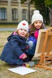 Kleine nette Mädchen zeichnet Farben auf einem Gestell Stockbild