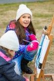 Kleine nette Mädchen zeichnet Farben auf einem Gestell Lizenzfreies Stockfoto