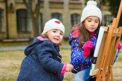 Kleine nette Mädchen zeichnet Farben auf einem Gestell Stockfoto