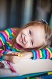 Kleine nette Mädchenmalerei mit Bleistiften während Stockfotos