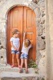 Kleine nette Schwestern nähern sich alter Tür im griechischen Dorf Lizenzfreies Stockfoto