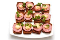 Kleine open sandwiches op witte plaat Stock Afbeelding