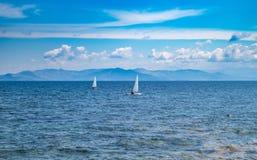 Kleine optimistenboten met witte zeilen, blauwe hemel en overzeese achtergrond royalty-vrije stock fotografie