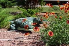 Kleine oranje bloemen op de achtergrond van een decoratieve groene krokodil Het bed van de bloem royalty-vrije stock afbeeldingen
