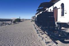 Kleine oude die trein in het zand wordt geplakt stock foto's