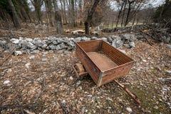 Kleine oude roestige aanhangwagen die zich dichtbij een steenmuur bevinden in het bos stock foto's