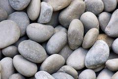 Kleine ovale graue Kiesel oder Steine Stockfotografie