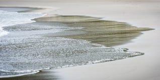 Kleine Ozeanmeereswellen auf sandigem Strand im ruhigen Wetter Stockbilder