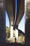 Kleine Person unter einer großen Brücke Lizenzfreies Stockfoto