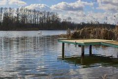 Kleine pijler op het meer, in de achtergrondzwanen Stock Afbeeldingen