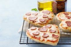 Kleine Pizzas mit Mozzarellakäse, -pepperonis, -tomate und -basilikum stockfotos