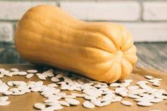 Kleine pompoen met zaden op keukenlijst Royalty-vrije Stock Afbeeldingen