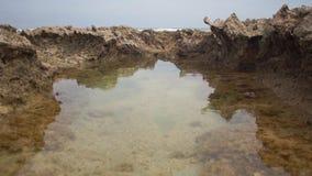 Kleine pool onder de rotsen tegen een grijze hemel stock videobeelden