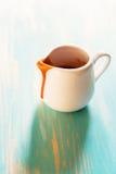Kleine porseleinwaterkruik met rozebotteljam Stock Fotografie