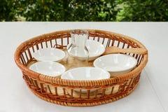 Kleine Porzellanschalen im Bambuskorb mit bokeh Hintergrund Lizenzfreie Stockfotos