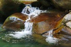 Kleine prachtige verfrissende watervallen onder de rotsen van bergkreek royalty-vrije stock afbeeldingen