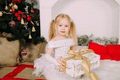 Kleine Prinzessin des Schnees, die Weihnachtsgeschenk hält Stockfoto