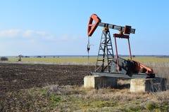 Kleine Pumpe Jack auf dem landwirtschaftlichen Gebiet Stockbilder