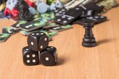Kleine Pyramide von schwarzen Würfeln von Würfeln auf dem Hintergrund von zerstreuten Gegenständen für Gesellschaftsspiele lizenzfreie stockfotografie