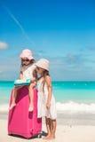 Kleine reizende Mädchen mit großem Koffer und einer Karte, die nach der Weise auf tropischem Strand sucht Stockfotos