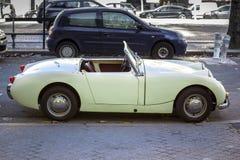 Kleine, retro cabrioauto Uitstekende die auto binnen in de stad wordt geparkeerd royalty-vrije stock fotografie