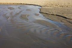Kleine rivier goot verlies van water Gebroken pijp gietend water op de kust van het strand, het overzees, op het zand stock afbeeldingen