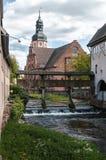 Kleine rivier met een dijk en een grote kerk in Ettlingen, Duitsland Stock Fotografie