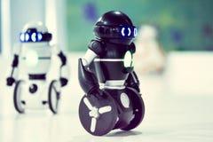 Kleine robots, humanoid met kleine wielen in plaats van benen en lichtgevende ogen royalty-vrije stock afbeelding