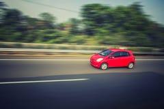 Kleine rode auto op de weg Stock Afbeeldingen