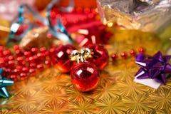 Kleine rode bal dichtbij gouden gift-doos rode parel en boog Royalty-vrije Stock Afbeelding