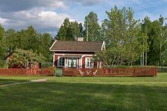 Kleine rode cabine met rode piketomheining in Fagersta, Zweden stock fotografie