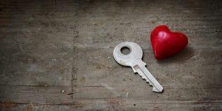 Kleine rode hartvorm en een zilveren sleutel op rustiek hout, concept F Royalty-vrije Stock Fotografie