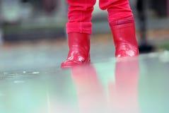 Kleine rode laarzen in de regen stock foto's
