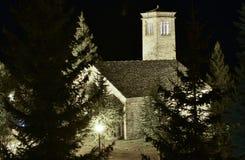 kleine Romanesquekirche mit seinem typischen Turm gemacht in allen Steinen mitten in einem Wald belichtet bis zum Nacht stockfotos