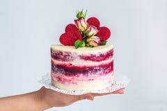 Kleine rood-witte cake op de palm, die met rozen en harten wordt verfraaid Stock Afbeeldingen