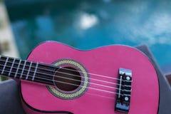 Kleine rosa Ukulelegitarre auf einem tropischen Hintergrund Ist ein wirklicher Seelenmusikinhalt lizenzfreies stockfoto