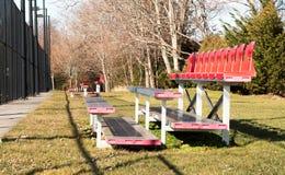 Kleine rote Zuschauertribünen durch Tennisplätze stockbild