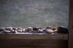 Kleine rotsen op een houten richelplank Stock Afbeeldingen