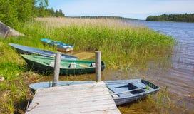 Kleine Ruderboote legen auf Küste von ruhigem See Lizenzfreie Stockbilder
